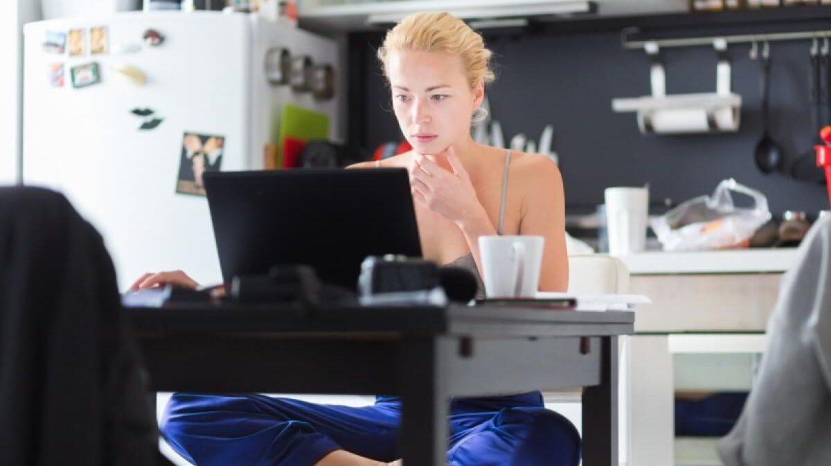 New Work: Frau arbeitet in Küche am Tisch mit Laptop